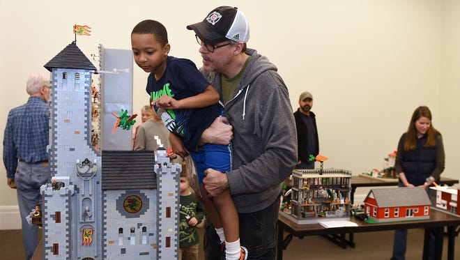 Josh Childs lifts his son Joses, 7, to see a castle made out of Legos during Nashville Public Library's sixth annual lego contest on Saturday Feb., 20, 2016. Some 283 contestants participated from age 2 to adult. A panel of judges will award first-place, runner-up, six categories on Sunday.