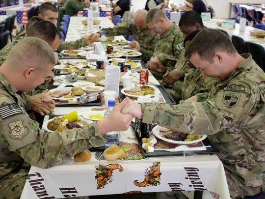 U.S. soldiers deployed to Kabul, Afghanistan, pray before eating a Thanksgiving meal at a dining hall in 2012. Many veterans say the deep friendships they developed during their deployments in the war-torn region remain highlights of their military service even as some remain conflicted about whether the mission has proven to be a success.