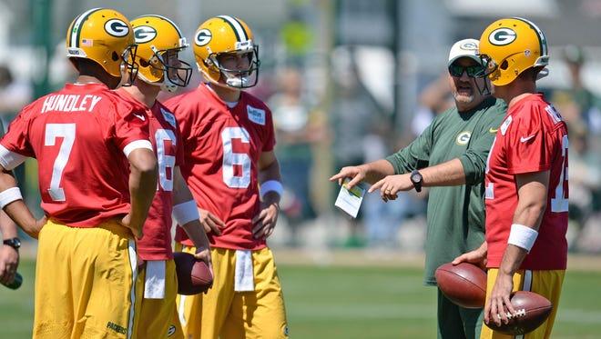 Green Bay Packers quarterbacks Brett Hundley (7), Scott Tolzien (16), Matt Blanchard (6) and Aaron Rodgers (12) talk with coach Alex Van Pelt during minicamp.