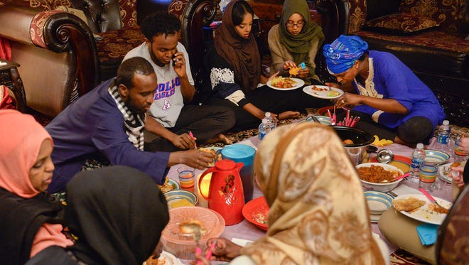 Katra Hethar, far left, and her family gather on the floor of her apartment to break their Ramadan fast Tuesday, June 7, 2016, in Waite Park.