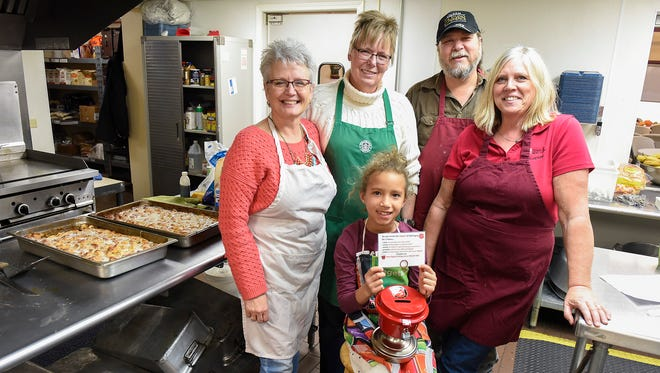 Volunteers Linda Henrichs, Chris Pederson, Bill Henrichs, Carla Rust and Ja'Leyah Ceaser, front, are challenging other volunteers this bell ringing season shown Thursday, Nov. 9, at the Salvation Army.