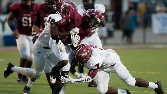 Prattville's De'Keith Whatley is stopped by Stanhope Elmore's Tywon Martin (7) and Barry Mitchell (10) at Stanley-Jensen Stadium in Prattville, Ala., on Friday August 28, 2015.
