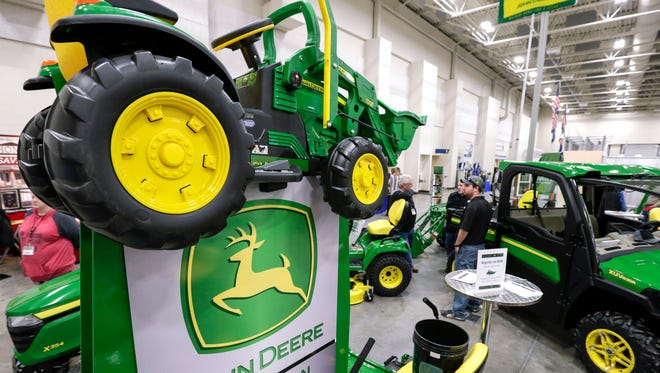 """John Deere products, including a toy tractor on the sign, are on display at the """"Spring into Spring"""" home and garden trade show in Council Bluffs, Iowa, Friday, Feb. 23, 2018."""