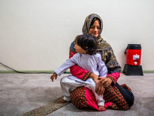 Nigi Kapadia holds her son Nyle, 2, while waiting for
