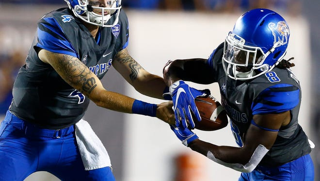 University of Memphis quarterback Riley Ferguson (left) hands off to running back Darrell Henderson (right) against the Southern Illinois University defense during first quarter action at the Liberty Bowl Memorial Stadium Saturday, September 23, 2017.