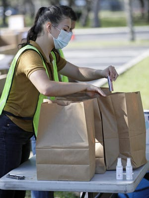 Volunteers pack personal protective equipment (PPE) items in bags including disposable face masks, reusable masks and hand sanitizer to be distributed to small businesses Wednesday, June 24, 2020, in Orlando. Volusia County announced they will be providing 7,000 PPE kits to small businesses starting next week.