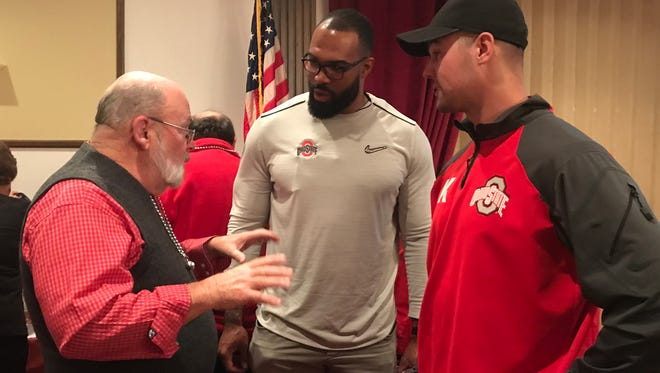 Former Buckeyes players Doug Worthington and Drew Basil take with fans of the team during the Buckeye Bash Monday.