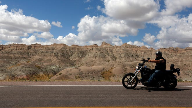 A lone biker drives the Badlands Loop in Badlands National Park on Monday, Aug. 7, 2017  in South Dakota. Badlands National Park is a popular day trip for motorcyclists in the state for the Sturgis Motorcycle Rally.   Thousands of bikers descend on the small South Dakota community each year for the Sturgis motorcycle rally.  (Chris Huber/Rapid City Journal via AP)