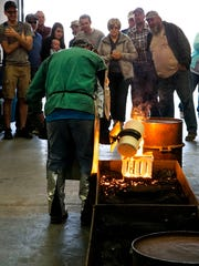 Jared Meibos pours melted metal into his cast of small