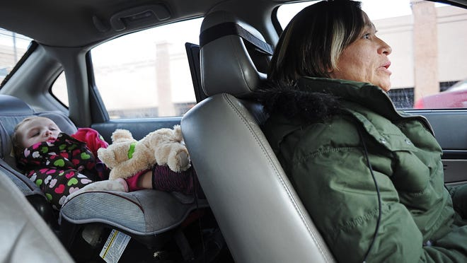 Sandee Dillon, of Sioux Falls, drives to Lincoln High School to pick up her daughter, Summer Rada, 16, Tuesday, Dec. 8, 2015, as her 17-month-old niece Journie Dillon, who she has custody of, sits in the back seat watching a movie in Sioux Falls. Dillon, who works at Family Dollar, is a single mother of six, including her niece.