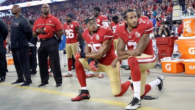 In this Sept. 12, 2016, file photo, San Francisco 49ers safety Eric Reid (35) and quarterback Colin Kaepernick (7) kneel during the national anthem before an NFL football game against the Los Angeles Rams in Santa Clara, Calif. Despite their vastly divergent methods, Colin Kaepernick and LeBron James helped set a stake in the ground, declaring to athletes across all sports that their platforms could be used for more than fun and games in the 21st century.