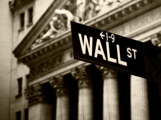 Wall Street street sign in front of New York Stock Exchange building.