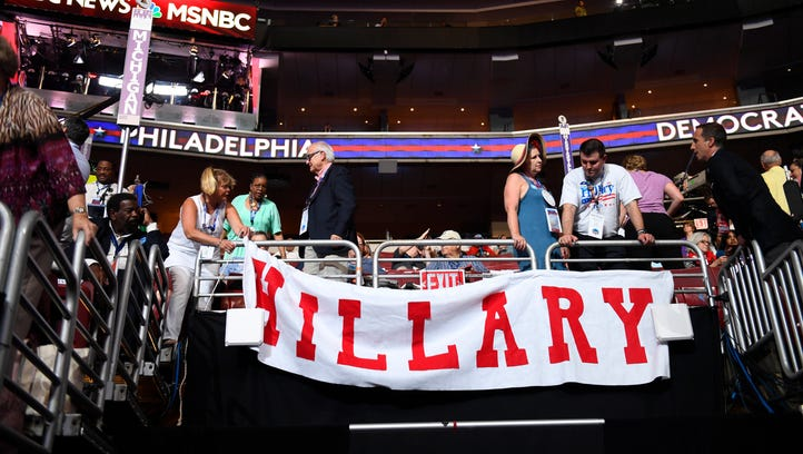 Convention-goers hang a banner before the start of