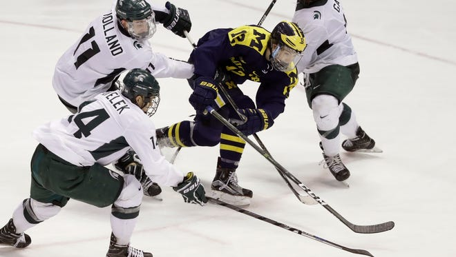 Michigan State forward Dylan Pavelek (14) steals the puck away from Michigan forward James Sanchez (12) during the third period of a Great Lakes Invitational consolation game Friday at Joe Louis Arena.
