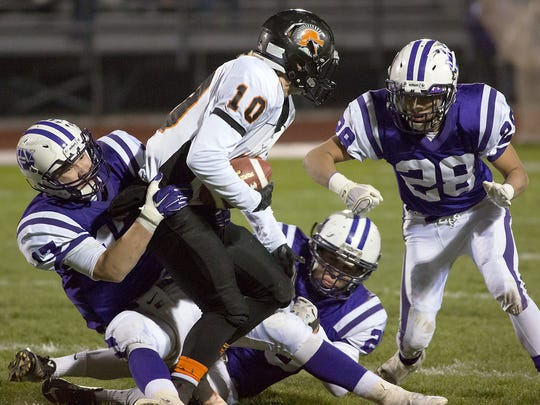 Northern's Curtis Robison drags down York Suburban's Collin Mailman.  Northern York defeated York Suburban 30-16 in the first round of District III playoffs Friday, Nov. 13, 2015.