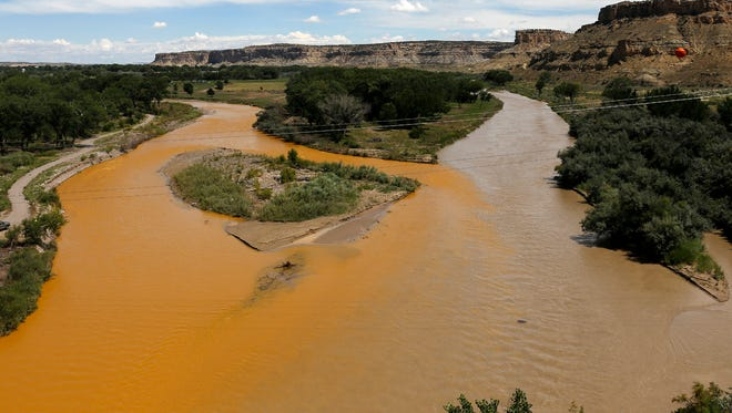 At left, the Animas River flows near its confluence with the San Juan River in Farmington on Aug. 8, 2015, shortly after the Gold Kine Mine near Silverton, Colo., was breached.