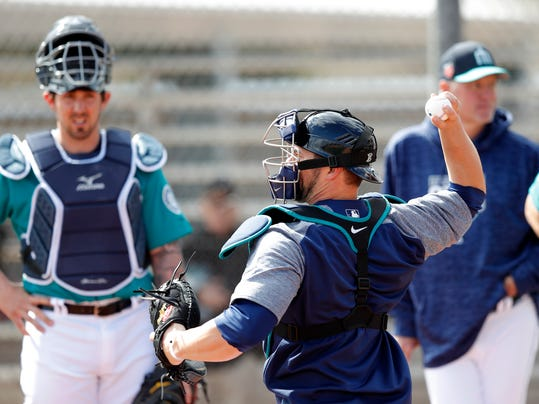Seattle Mariners catcher Mike Zunino, right, throws to second base during a baseball spring training workout, Monday, Feb. 19, 2018, in Peoria, Ariz. (AP Photo/Charlie Neibergall)