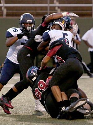 Several Wichita Falls High defenders tackle Arlington Heights' Darius McCloud (5) and nearly knock off McCloud's helmet on Sept. 15 at Memorial Stadium.
