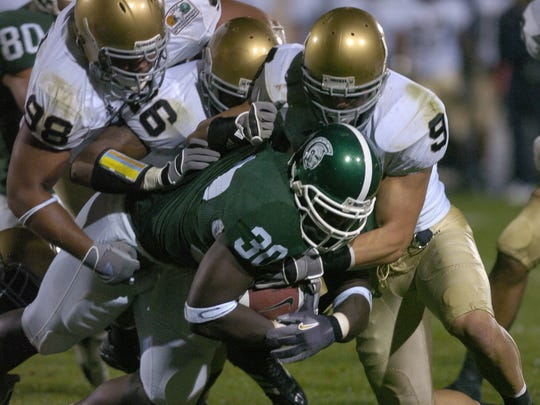 MSU running back Jehuu Caulcrick is gang-tackled by