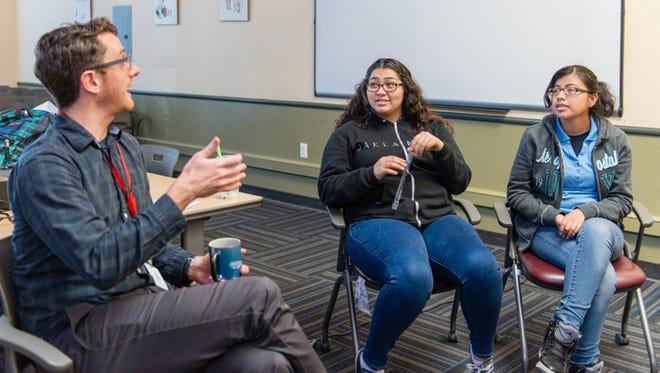 Eric Waters, coordinator for the behavioral health program at the Life Academy High School leads a discussion with Fernanda May, 17, and Graciela Perez, 17, at La Clínica de la Raza in Oakland, Calif., on Jan. 27, 2016. The program provides training in mental health first aid and places students in internships with mental health organizations.