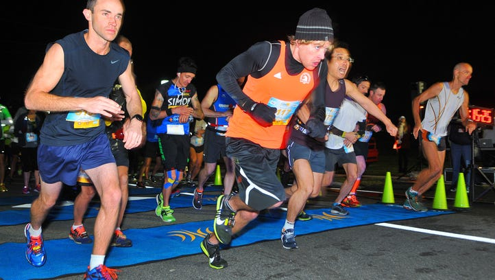 Marathon runner Tory Johansen of Melbourne (orange) gets a great off the starting line to win the Publix Florida Marathon as runners brave the cold weather during Sunday mornings Publix Florida Marathon and half Marathon held in Melbourne.
