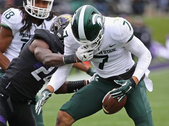 Michigan State's Cody White fumbles as he's hit by Northwestern's Montre Hartage at Ryan Field on Saturday, Oct. 28, 2017 in Evanston, Ill.