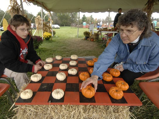 Visitors play mini-pumpkin checkers during Willow Springs