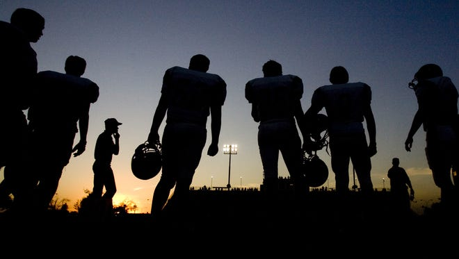Round Valley football players and coaches are silhouetted against the setting sun during the first quarter of Friday's game against Coolidge in 2007.