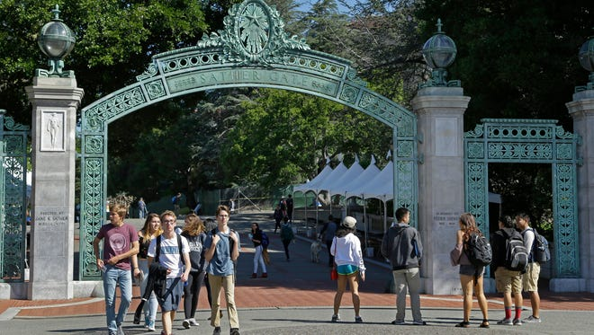 """Students walk past Sather Gate on the University of California-Berkeley campus on April 21, 2017. The campus is bracing for a showdown when the conservative provocateur Ann Coulter has vowed to speak in defiance of the university's wishes. Officials, police and the campus Republicans who invited Coulter say there are valid concerns for violence in what is being called an ongoing """"Battle of Berkeley."""""""