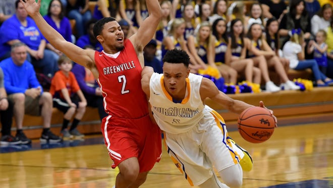 Wren's Trey McGowens, right, drives to the basket while defended by Greenville's Kaelin Braswell during the first half of the Hurricanes' 69-48 win over the visiting Red Raiders Friday night.