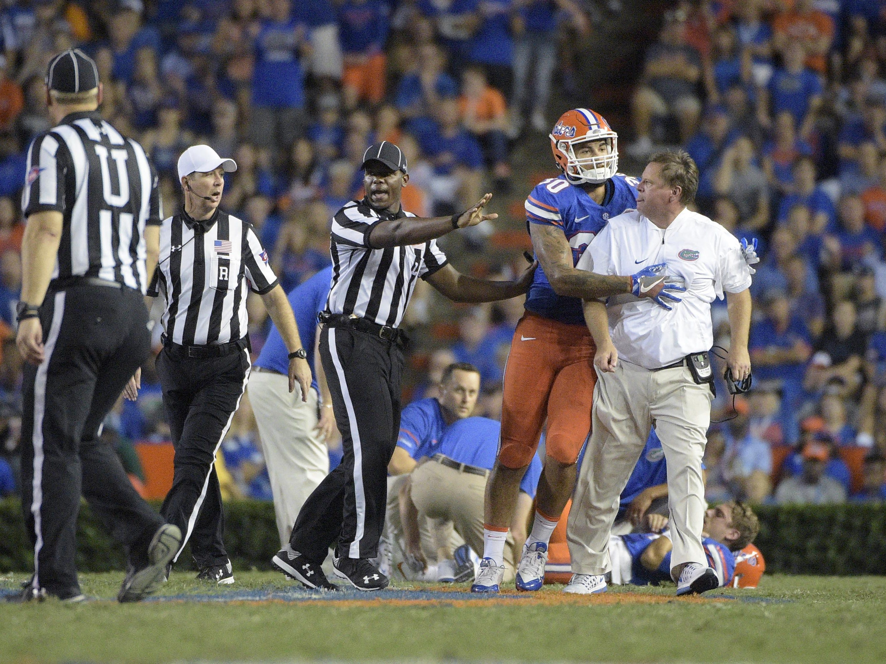 Florida head coach Jim McElwain, right, is restrained by tight end DeAndre Goolsby (30) and officials after McElwain showed his displeasure after quarterback Luke Del Rio was knocked out of the game on a hit during the second half of an NCAA college football game against North Texas in Gainesville, Fla., Saturday, Sept. 17, 2016. North Texas was penalized for roughing the passer. (AP Photo/Phelan M. Ebenhack)