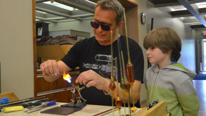 Joe Takens prepares to create glass art as his son, Bryer Takens, 6, looks on at Friday's Spring into the Arts.