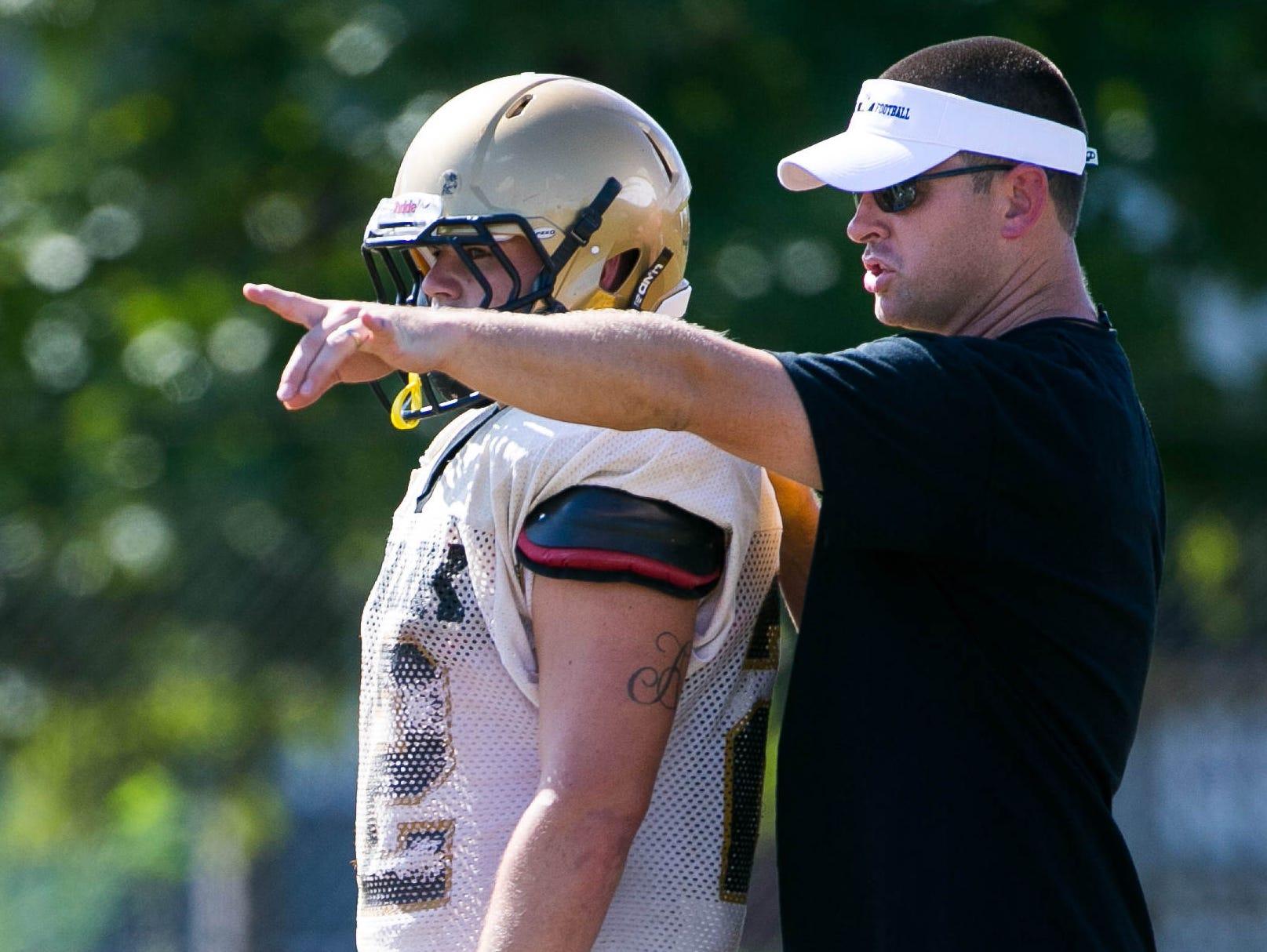 New Newark High football coach Barry Zehnder runs his team through drills during practice on Tuesday.