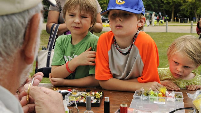 Landon Austin, left, Blake O'Hara and his sister Erynn watch Dave Kollmann of the St. Cloud Fly Anglers tie a lure during the 2013 Take A Day OFF on the Mississippi.