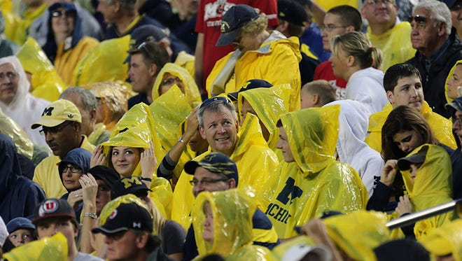 Fans in the stands get ready for the rain Saturday at Michigan Stadium.