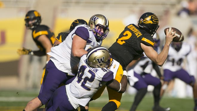 Washington defensive tackle Greg Gaines (left) and linebacker Cory Littleton (42) pressure ASU quarterback Mike Bercovici during the second quarter of the college football game at Sun Devil Stadium in Tempe on Saturday, November 14, 2015.