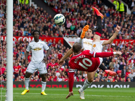 Manchester United's Wayne Rooney, bottom right, scores against Swansea City during their English Premier League soccer match at Old Trafford Stadium, Manchester, England, Saturday Aug. 16, 2014. (AP Photo/Jon Super)