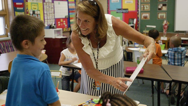 Longfellow Elementary School second grade teacher Juli Coffey helps student Luciano Krutke with an activity on the first day of school Tuesday, Sept. 1, 2015.