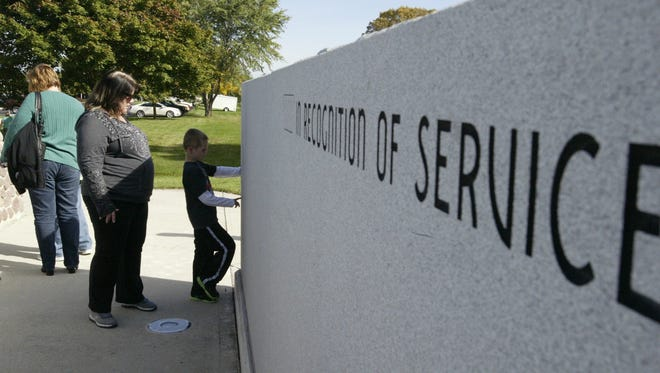A young boy looks points to a recently inscribed name of a veteran following the rededication of the Sheboygan County Veterans Memorial on October 10, 2015.