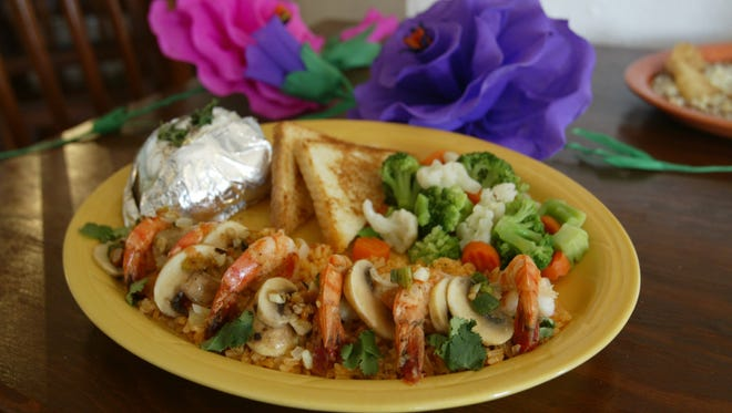 The Camaron al Mojo de Ajo at Meson de Oñate, 9993 Soccorro Road, comes with shrimp served over a bed of mushroom rice, toast, mixed vegetables and a baked potato.