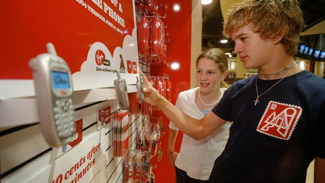 Sam Best and his sister Annie visit The Virgin Mega Store in New York's Times Square to look at the Virgin Mobile cellular phone system. Virgin sells cell phone time by the minute instead of on a monthly plan and offers a selection of specialty phones, all designed to appeal to teens and low income customers.