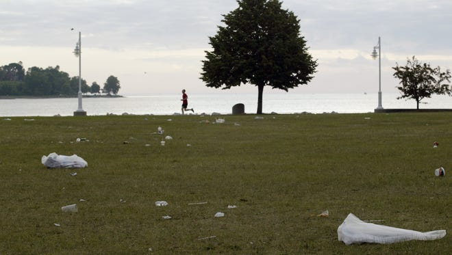 A city of Sheboygan crew picks up trash along the beach at Deland Park on July 5. The beach and park were left littered with trash after the fireworks on July 4.