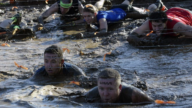 Participants crawl through the Kiss of Mud obstacle at Tough Mudder Wisconsin in Elkhart Lake on Sept. 12, 2015.