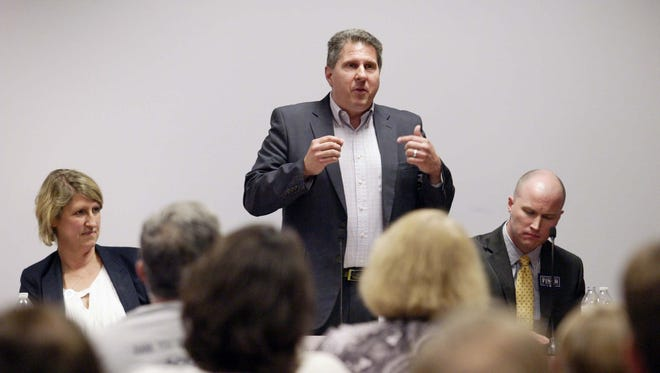 Bryan Kennedy, standing, gestures during a debate against Martha Laning, left, and Eric Finch, right, Tuesday night in Sheboygan's Mead Public Library. The three are competing to chair the state's Democratic Party. A fourth candidate, Joe Donovan, wasn't at the event.