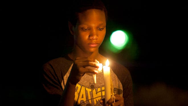 Christian Ross, 13, lights a candle after a candlelight vigil Friday night in Sheboygan. About 125 people lit candles and sang songs Friday night at a candlelight vigil in Sheboygan following violent protests a week earlier in Virginia.