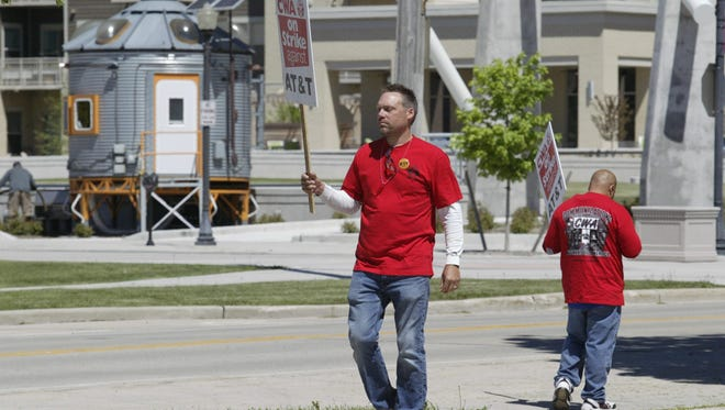A small group of protesters carried signs outside an AT&T building near downtown Sheboygan Friday, June 1, 2018, as part of a union strike against the telecommunications giant.