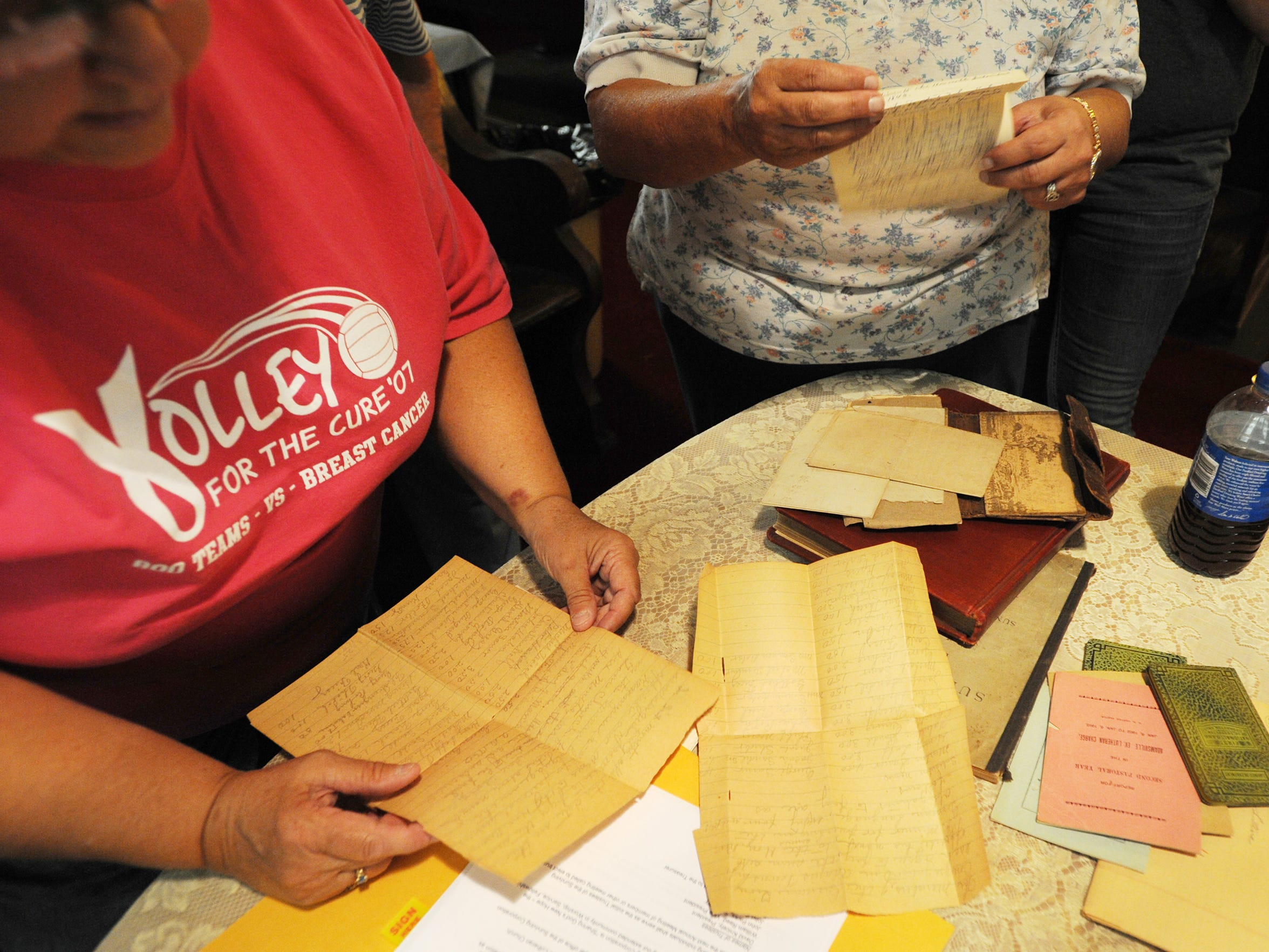 Pam Thomas, left, and Kaye Morgan look through old letters found while cleaning out Zion Lutheran Church a few days before the church's final service.