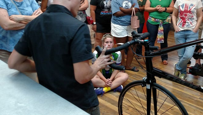 Hank showing cyclists how to adjust brakes.