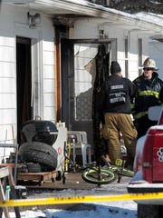 Goshen Township Fire Chief Steve Pegram (right) talks with a fire investigator at the scene of a fatal fire on Stella Drive.