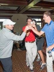 Louisiana Tech golf coach Jeff Jenkins, left, reacts with his players following Thursday's NCAA Regionals announcement on the Golf Channel.